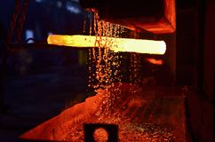 El proceso de forjar el metal en la producción de productos de metal moldeados pesados imagenes de archivo