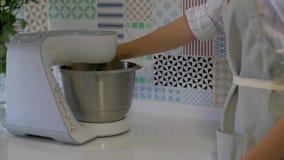 El proceso de hacer la crema para una torta El chef de repostería está batiendo la crema con una máquina de la licuadora almacen de video