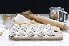 El proceso de hacer las bolas de masa hervida hechas en casa Bolas de masa hervida hechas en casa crudas en un tablero de madera foto de archivo libre de regalías