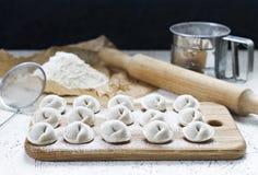 El proceso de hacer las bolas de masa hervida hechas en casa Bolas de masa hervida hechas en casa crudas en un tablero de madera imagen de archivo libre de regalías