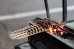 El proceso de hacer el pollo satay por los vendedores ambulantes usando el fuego del carb?n de le?a foto de archivo libre de regalías