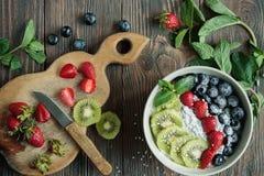 El proceso de hacer un smoothie de la fruta un cuenco de fresas, del kiwi y de los arándanos para un desayuno sano foto de archivo