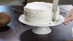 El proceso de hacer una torta Los confiteros comparan la crema de la galleta usando la espátula de los pasteles
