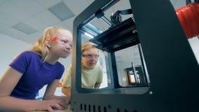 el proceso de impresión 3D se está mostrando a dos niños almacen de video