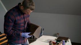 El proceso de la fabricación una cartera de cuero hecha a mano El amo examina un pedazo de cuero pintado handmade