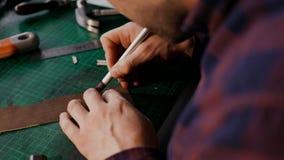 El proceso de la fabricación una cartera de cuero hecha a mano El artesano cortó un pedazo de cuero Mercancías de cuero hechas a