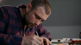 El proceso de la fabricación una cartera de cuero hecha a mano El mago hace una marca en la corteza de cuero Poseer negocio