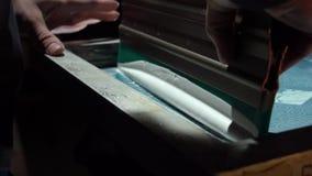 El proceso de la impresión de pantalla de seda Concepto de fabricante handcrafted de la marca metrajes