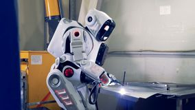 El proceso de la soldadura de una hoja de metal se realizó por a humano-como el robot en un piso de la fábrica almacen de video