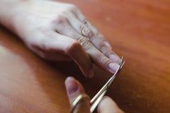 El proceso de las tijeras del clippingl del clavo Concepto del cuidado de la mano foto de archivo libre de regalías