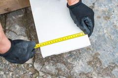 El proceso de medir la longitud de una hoja de la mampostería seca Fotos de archivo libres de regalías