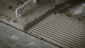 El proceso de nivelar el cemento con una espátula, el capataz celebra una herramienta en su mano y los dirige con almacen de metraje de vídeo