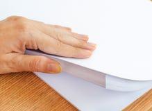El proceso de paginar el papel blanco de la oficina con sus fingeres Imagen de archivo libre de regalías