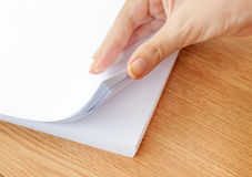 El proceso de paginar el papel blanco de la oficina con sus fingeres Foto de archivo
