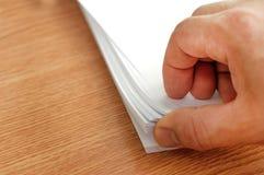 El proceso de paginar el papel blanco de la oficina con sus fingeres Fotografía de archivo libre de regalías