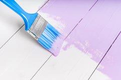 El proceso de pintar la madera sube con el cepillo y el color violeta Imagen de archivo