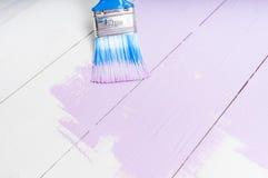 El proceso de pintar la madera sube con el cepillo y el color violeta Foto de archivo libre de regalías