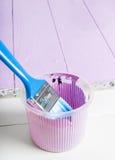 El proceso de pintar la madera sube con el cepillo y el color violeta Imagen de archivo libre de regalías