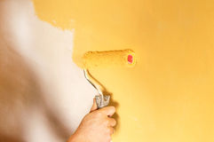 El proceso de pintar las paredes en color amarillo Foto de archivo libre de regalías
