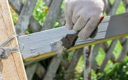 El proceso de pintar una capa de madera con un cepillo con la pintura gris foto de archivo libre de regalías