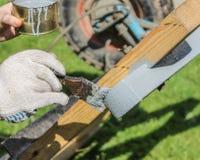 El proceso de pintar una capa de madera con un cepillo con la pintura gris imagen de archivo libre de regalías