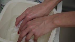 El proceso de preparar los trapos mojados para limpiar la piel Manos de un cierre del cosmet?logo para arriba Soluci?n acuosa en  metrajes