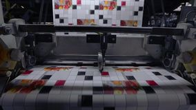 El proceso de producir el papel pintado, cortando la cinta del papel pintado en dos porciones Transportador en la planta para la  metrajes