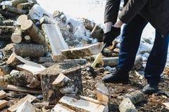 El proceso de saltar el registro de madera con un hacha en la primavera temprana imagen de archivo