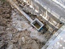 El proceso que entierra el tubo del drenaje alrededor del edificio imágenes de archivo libres de regalías