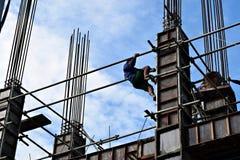El productor de acero filipino de la construcción que sube abajo usando el andamio instala tubos en el edificio alto foto de archivo