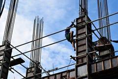 El productor de acero filipino de la construcción que sube abajo usando el andamio instala tubos en el edificio alto Imágenes de archivo libres de regalías