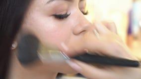 El profesional compone al artista que aplica el cosmético en cara de la muchacha adolescente linda para la tez del cuidado y de l almacen de video