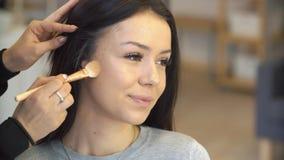 El profesional compone al artista que aplica el cosmético en cara de la muchacha adolescente linda para la tez del cuidado y de l almacen de metraje de vídeo