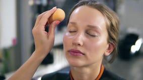 El profesional compone el amo que pone la crema de fundación en una cara Componga el proceso Ciérrese para arriba de una cara de  almacen de video