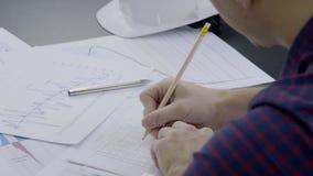 El profesional masculino trabaja con la documentación del proyecto en oficina moderna almacen de video