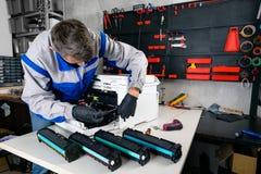 El profesional principal rellena cartuchos de la impresora laser en el taller fotos de archivo libres de regalías