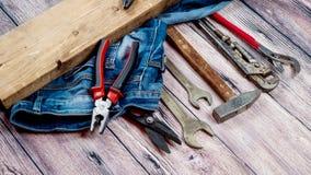 El profesional que reparaba los instrumentos para la renovación de adornamiento y constructiva fijó en el fondo de madera Fotos de archivo libres de regalías