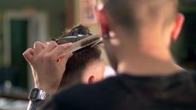 El profesional tatuó al peluquero que daba un nuevo corte de pelo a su cliente en una barbería almacen de metraje de vídeo