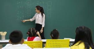 El profesor asi?tico escribe el problema de matem?ticas en tablero verde almacen de video