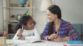 El profesor caucásico está ayudando a la muchacha de la raza mixta en escuela almacen de video