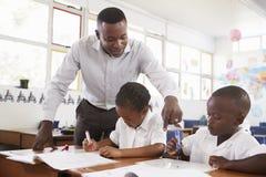 El profesor coloca a niños de ayuda de la escuela primaria en sus escritorios imagen de archivo