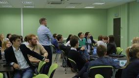 El profesor con los estudiantes mira la imagen del proyector y analiza el informationon financiero una lección en almacen de video