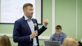 El profesor da conferencias en la economía en universidad Con el micrófono a disposición y con la ayuda de gestos, él transporta  almacen de video