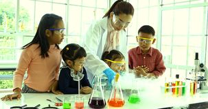El profesor de ciencias enseña a estudiantes asiáticos sobre las sustancias químicas, flotador del humo hacia fuera del cuenco almacen de video