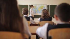 El profesor de la geografía dice a estudiantes en la clase el tema de la lección y hace preguntas a los estudiantes almacen de metraje de vídeo