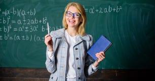 El profesor de la mujer con el libro delante de la pizarra piensa en trabajo Enseñe a las estrategias de proceso de la cognición  imagen de archivo