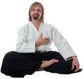 El profesor de la pacificación del aikido se sienta en suelo y la PU imágenes de archivo libres de regalías