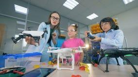 El profesor de la tecnología está dando instrucciones a niños en cómo controlar un quadcopter, abejón metrajes