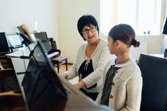 El profesor de música explica alegre cómo jugar el piano Imagen de archivo