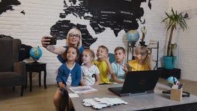 El profesor de sexo femenino feliz con los alumnos es el sentarse del escritorio y presenta para el selfie en clase de la geograf metrajes
